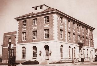 Sepia tone image of three story brick building